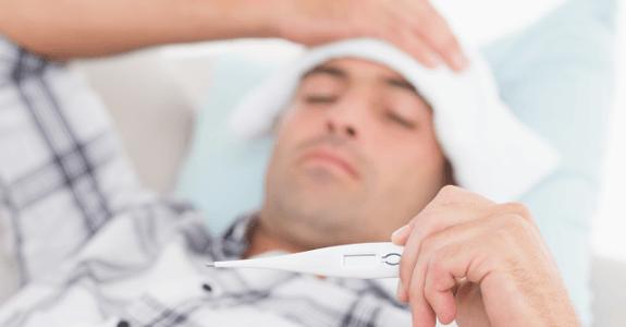 Ležiaci chorý muž s teplomerom