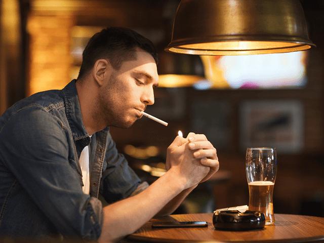 Muž fajčí a pije alkohol