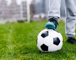 Dieťa s futbalovou loptou na ihrisku