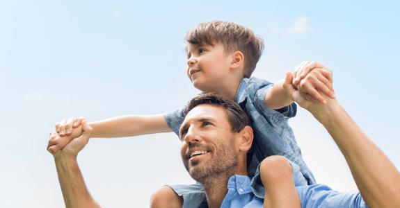 Otec nosí syna na ramenách
