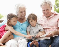 Deti so starými rodičmi čítajú knihu
